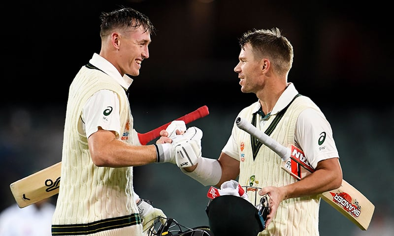 Australian batsmen Marnus Labuschagne (L) and David Warner (R) congratulate each other after their partnership against Pakistan on the first day of the second cricket Test match in Adelaide on Friday. — AFP
