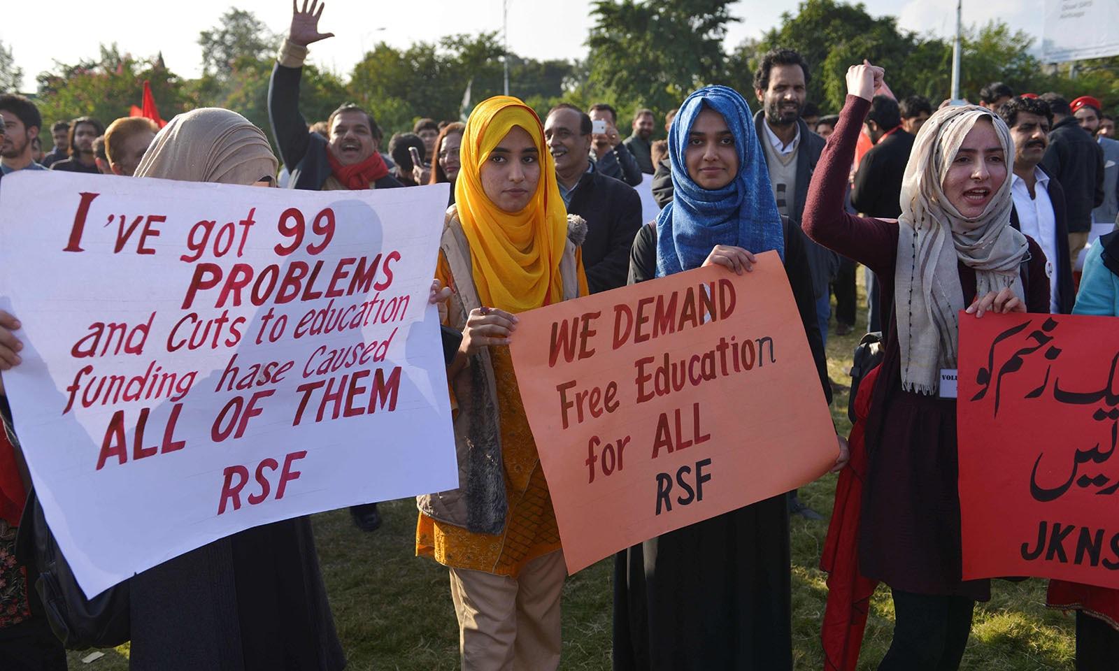 ایک پلے کارڈ پر لکھا تھا کہ تمام مسائل کی وجہ تعلیم کے بجٹ میں کمی ہے — فوٹو: اے ایف پی