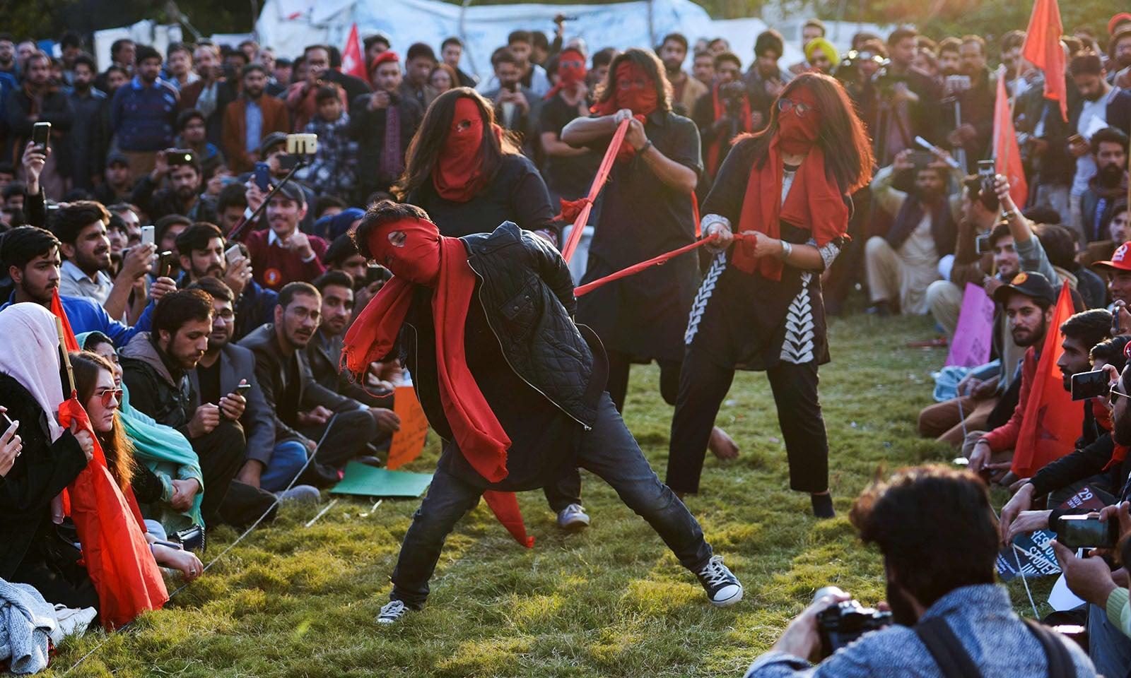 اسلام آباد میں ہونے والے مارچ میں تھیٹر پلے کے ذریعے مظاہرین نے تعلیم کی اہمیت کو اجاگر کیا — فوٹو: اے ایف پی