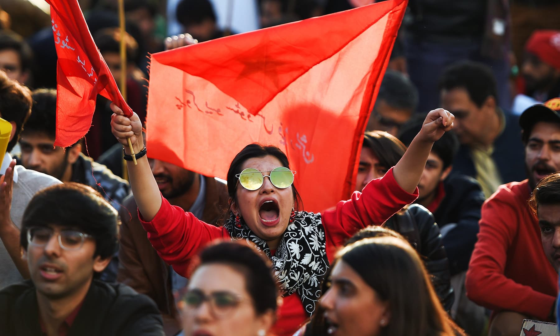 Students waved red flags and chanted slogans demanding more freedom for students, in Islamabad on Friday. — AFP