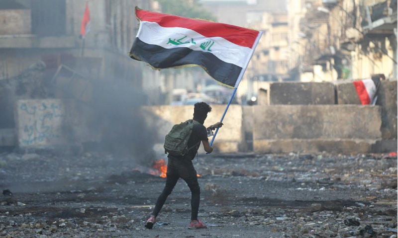 An Iraqi anti-government protester waves a national flag close to a concrete barricade amidst clashes with security forces along Baghdad's Rasheed Street on Friday.—AFP