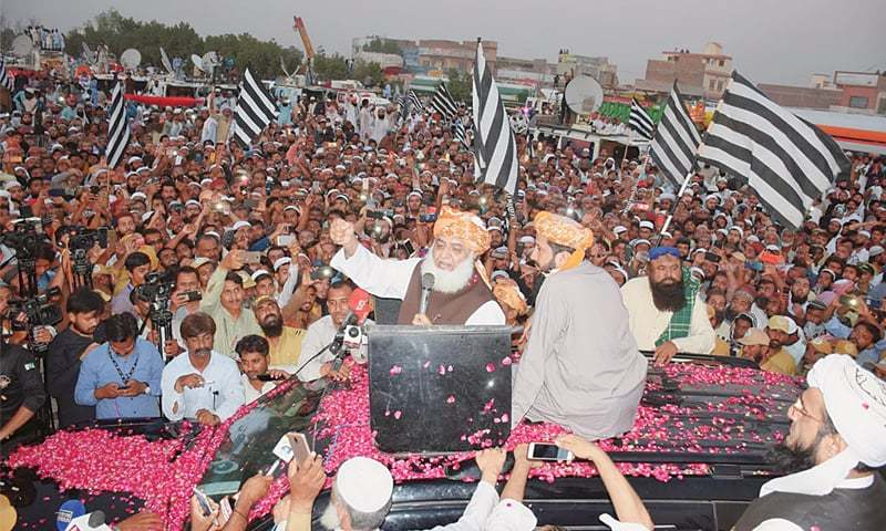JUI-F chief Maulana Fazlur Rehman waves to his supporters at Hyderabad bypass on  Oct 27. — Dawn/File