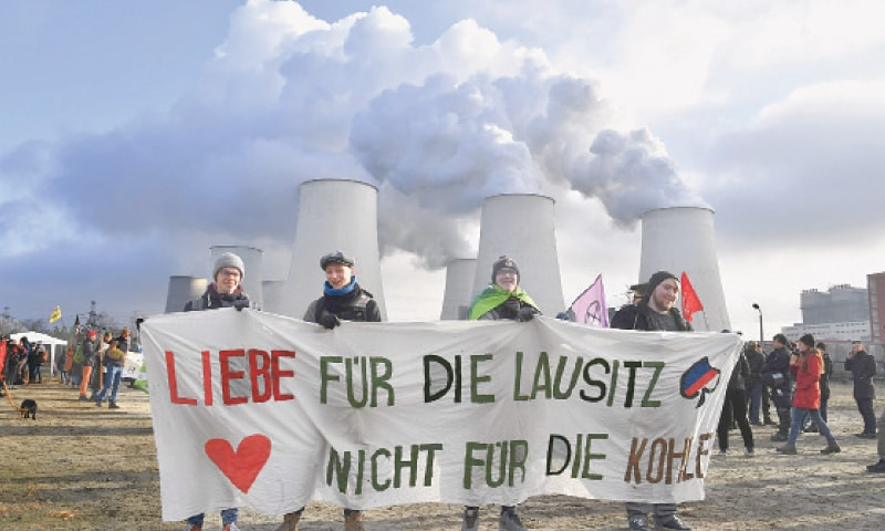"CLIMATE activists hold a placard reading ""Love for Lausitz, not for the coal"" during a demonstration in front of the Jaenschwalde power plant in eastern Germany on Saturday. Campaigners were preparing to occupy a vast opencast coal mine in eastern Germany to put pressure on the government to phase out the fossil fuel — a divisive issue in the country's rust belt. The occupation is being supported by other environmental groups, including the German branch of Fridays for Future which is organising its own protest in front of a nearby power station.—AFP"