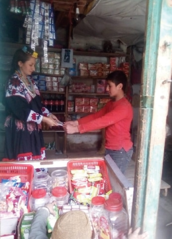 A Kalash woman deals with a customer at her shop in Krakal village of Bumburate valley. — Dawn
