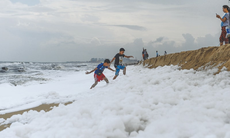 CHENNAI: Children play over foamy discharge on a beach.—AFP