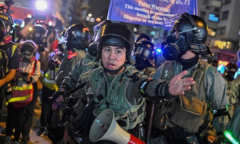A police officer gestures towards the media during a protest at Hung Hom in Hong Kong on December 1. — AFP