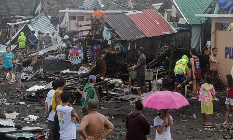 Residents stand among their damaged houses after Typhoon Kammuri hit Legazpi City, Albay, Philippines on  December 2. — Reuters