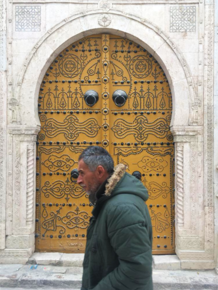 A man passes by a door with black studded nails.