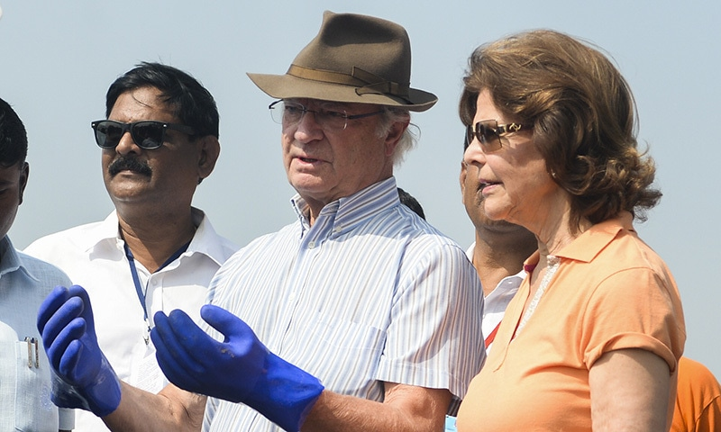 Sweden's King Carl XVI Gustaf (C) speaks with volunteers as Queen Silvia (R) looks on as they participate in a beach clean-up project a the Versova Beach in Mumbai on December 4. — AFP