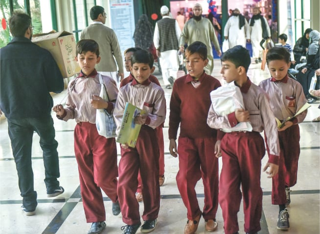 Schoolgirls browse through Urdu titles while (right) schoolboys walk off with newly bought books at the KIBF on Thursday.—White Star
