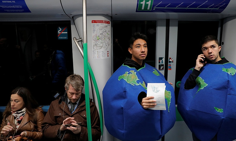 Young men dressed in earth costumes ride the metro towards the venue of the UN climate change conference (COP25) to deliver leaflets promoting public transport to reduce pollution in Madrid, Spain, December 5. — Reuters