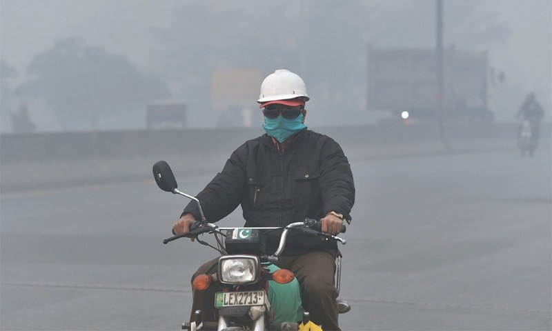 In this file photo, a commuter rides his motorbike amid heavy smog enveloping the provincial capital. —AFP