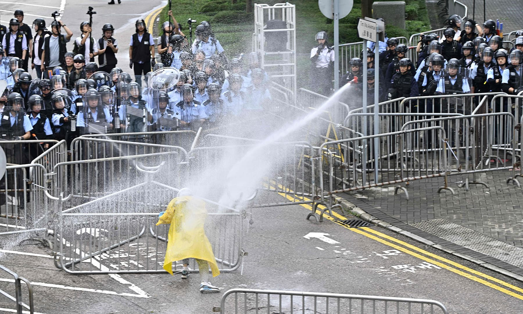 Police officers use pepper spray on a lone protestor near the government headquarters in Hong Kong on June 12. — AFP