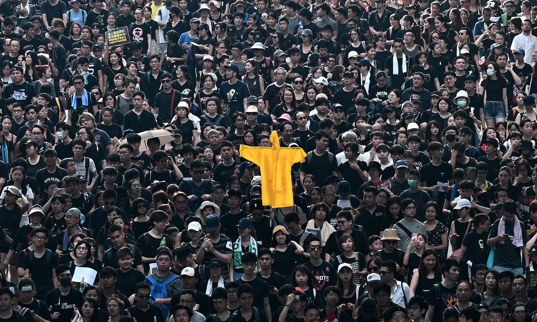 Protesters hold up a yellow raincoat in memory of a fellow protester who fell to his death the night before as they march at new rally against a controversial extradition law proposal in Hong Kong on June 16. — AFP