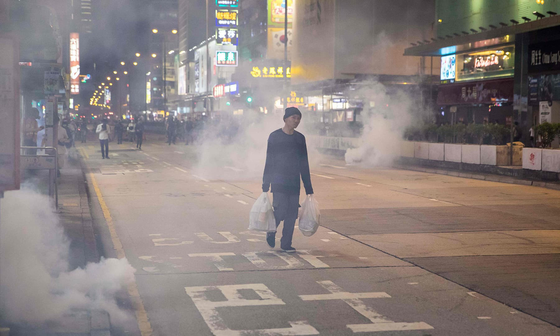 A man walks amongst tear gas fired by police to disperse pro-democracy protesters in the Mong Kok district in Hong Kong on October 27. — AFP