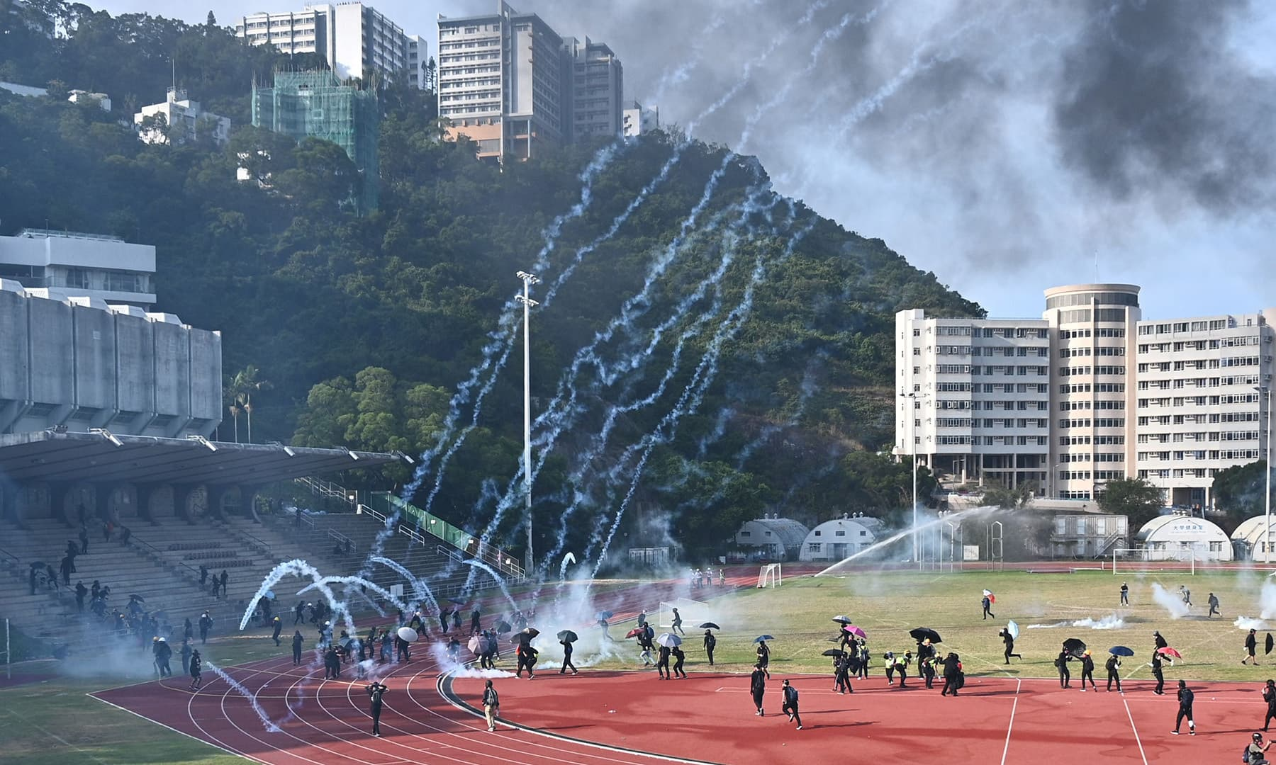 Protesters react after police fired tear gas at the Chinese University of Hong Kong (CUHK), in Hong Kong on November 12. — AFP