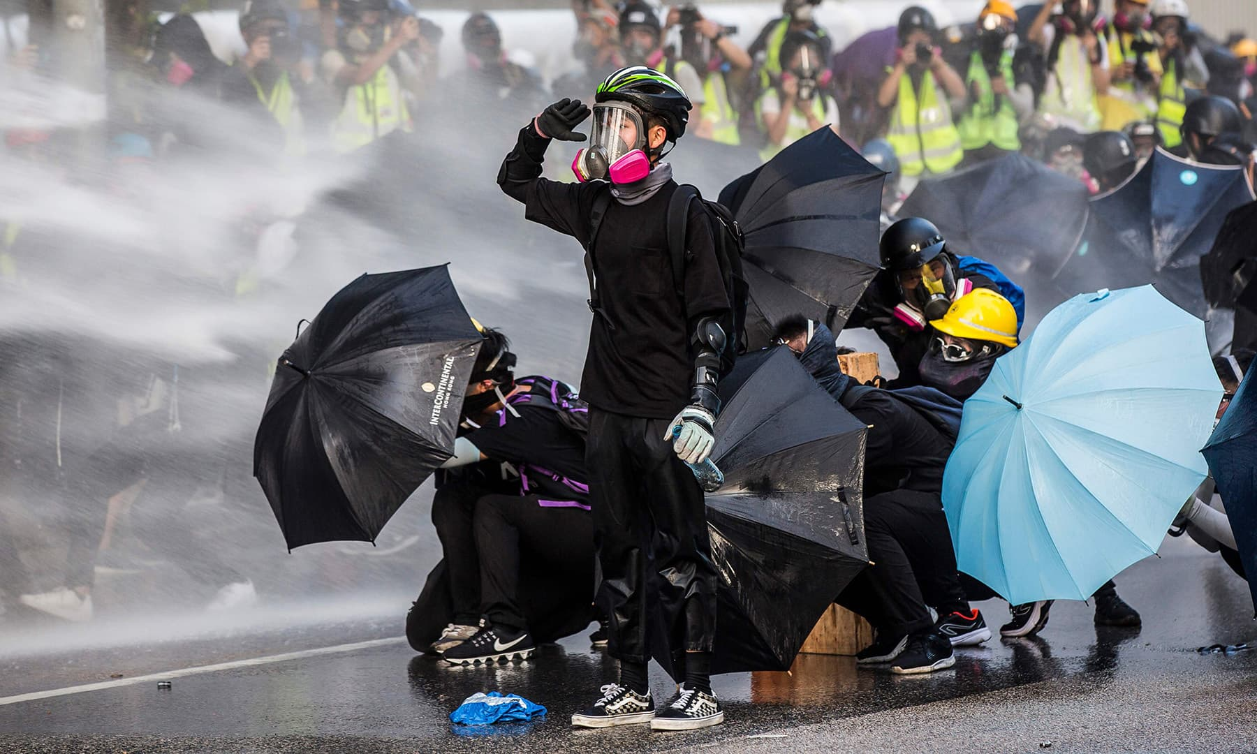 Pro-democracy protesters react as police fire water cannons outside the government headquarters in Hong Kong on September 15. — AFP