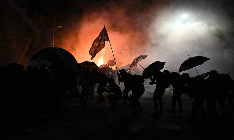 (FILES) In this file photo taken on November 12, 2019, protesters take cover during clashes with police at the Chinese University of Hong Kong (CUHK), in Hong Kong. - Some of them have lost their jobs, suffered life-changing injuries and even been forced into exile. But six months into Hong Kong's demonstrations, pro-democracy protesters say they aren't backing down. (Photo by Philip FONG / AFP) / TO GO WITH HongKong-China-politics-unrest,FOCUS by Su Xinqi and Yan Zhao — AFP or licensors