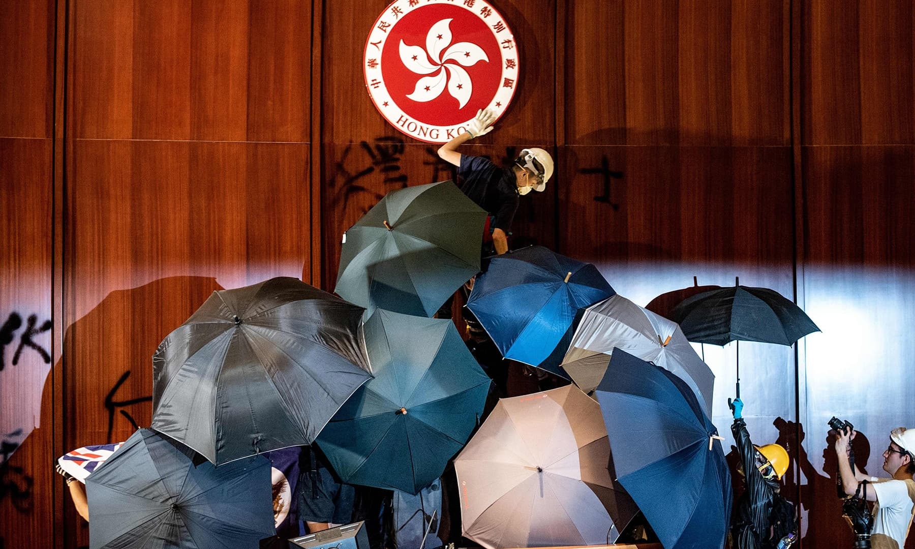 A protester defaces the Hong Kong emblem after protesters broke into the government headquarters in Hong Kong on July 1. — AFP