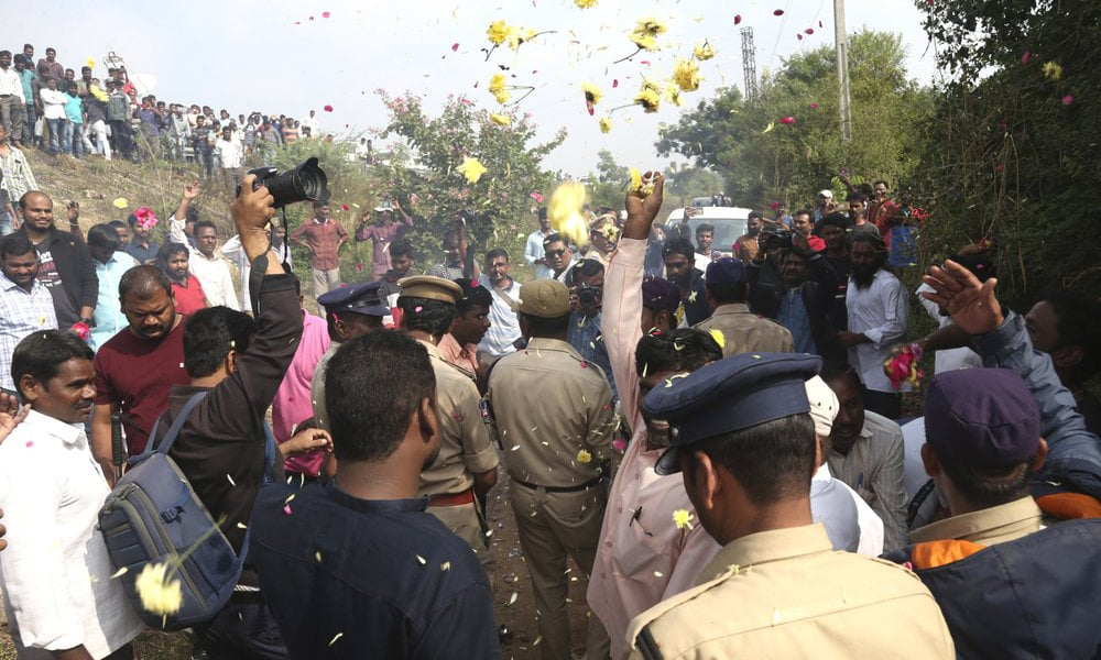 People throw flower petals on the Indian policemen guarding the area where rape accused were shot, in Shadnagar some 50 kilometers from Hyderabad, on Dec 6. — AP