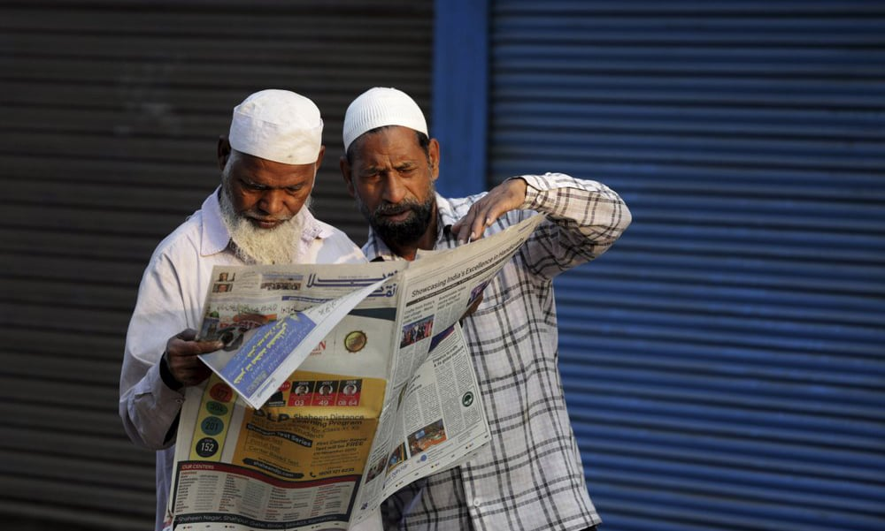 In this Nov 10 file photo, Muslims read about the verdict in a decades-old land title dispute between Muslims and Hindus in a newspaper in Ayodhya, India. — AP