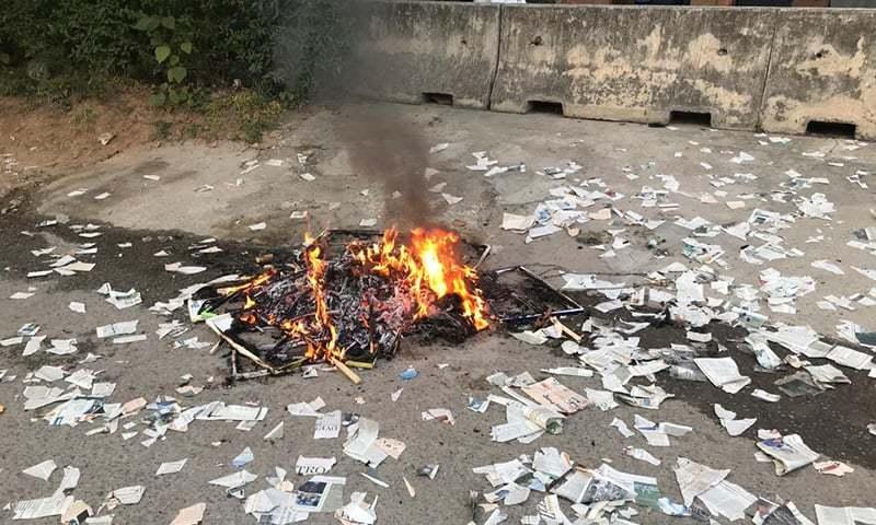 مظاہرین نے دفتر کے باہر ڈان اخبار کی کاپیاں بھی نذر آتش کیں— فوٹو: نوید صدیقی