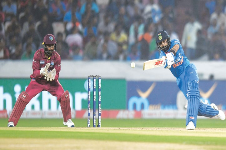 INDIAN captain Virat Kohli drives during the first T20 International against West Indies at the Rajiv Gandhi International Cricket Stadium on Friday.—AFP