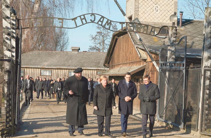 Oswiecim (Poland): German Chancellor Angela Merkel (second left) is flanked by Polish Prime Minister Mateusz Morawiecki and the director of the Auschwitz-Birkenau museum as she walks through the gate.—AFP