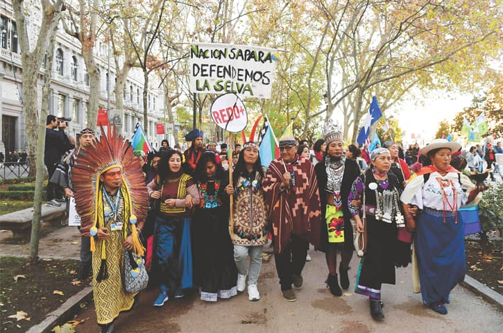 Madrid: People from indigenous communities take part in a climate march to call for urgent action from world leaders attending the COP25 summit.—AFP