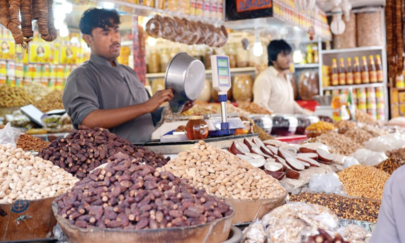 A shopkeeper weigh a bag of dry fruit. Officially imports of dry fruits have gone down but smuggled items are easily available all over the country.—Dawn