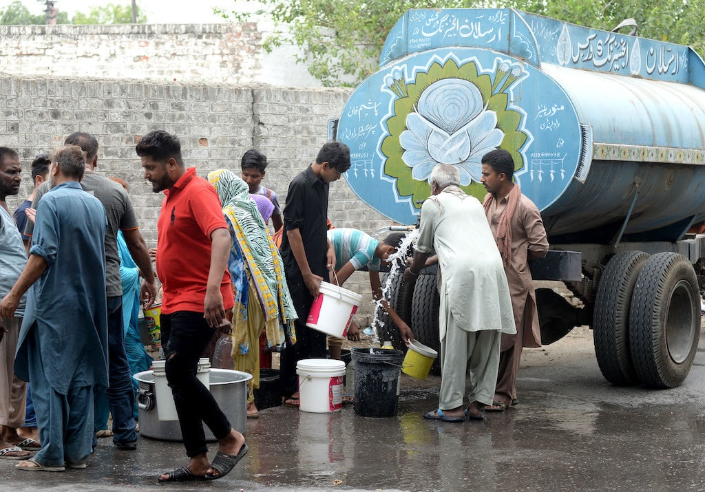 People gather around a water tanker to fill their buckets with water in Rawalpindi | Mohammad Asim/White Star