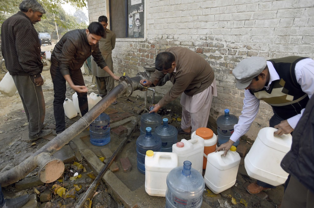 People fill cans with water from a makeshift hydrant | Tanveer Shahzad/White Star