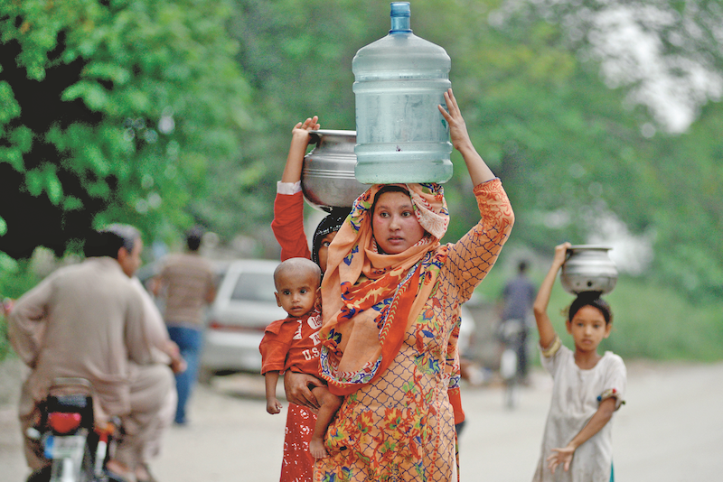 A woman and her daughter balance utensils as they walk home after collecting water in G-7 in Islamabad | Mohammad Asim/White Star