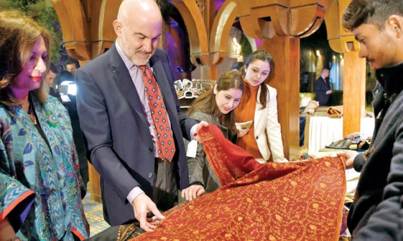 Visitors study a Kashmiri shawl at a stall in Arts and Crafts Festival. — White Star