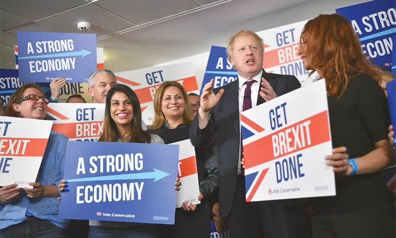 BRITISH Prime Minister Boris Johnson speaks to activists and supporters as he poses for a photograph at the Conservative party's election headquarters on Sunday.—AP