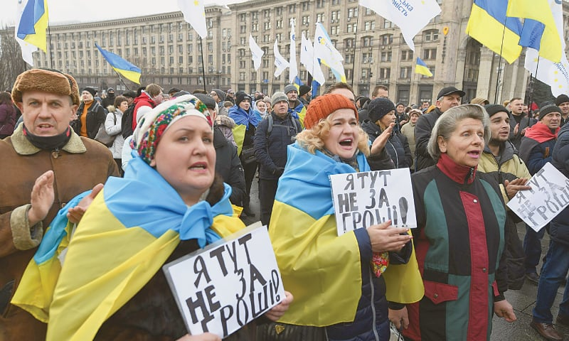 "Kiev: People take part in a rally, ""Red lines for ZE"" (nickname of the Ukrainian president) to call for ""no capitulation"" to Russia on the eve of  a summit between Ukraine and Russia in Paris on Monday. The French  president and the German chancellor will moderate the summit, aimed at ending five years of fighting between the two countries. —AFP"