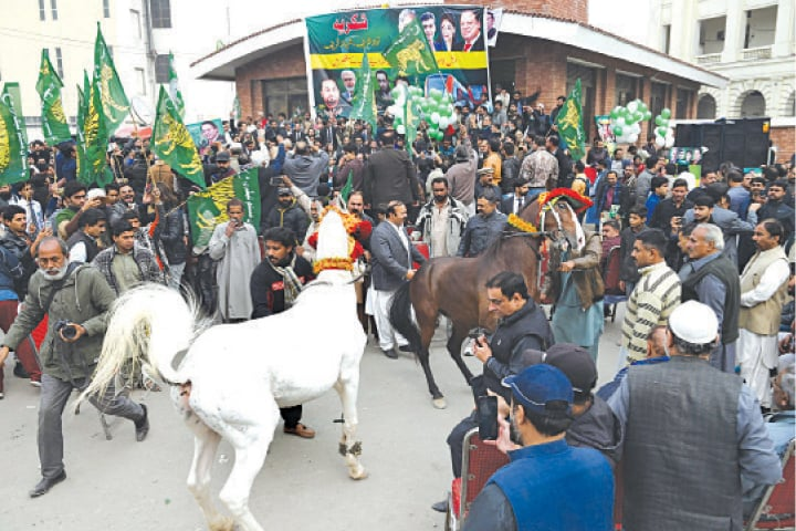 PML-N activists celebrate opening of Orange Line train in a 'mock ceremony' at GPO Chowk. — White Star