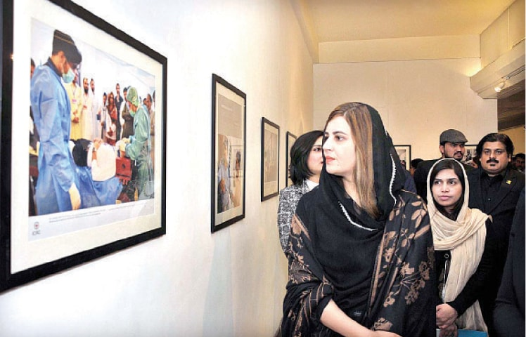 Minister of State for Climate Change Zartaj Gul looks at a photograph at the ICRC exhibition on Monday. — APP