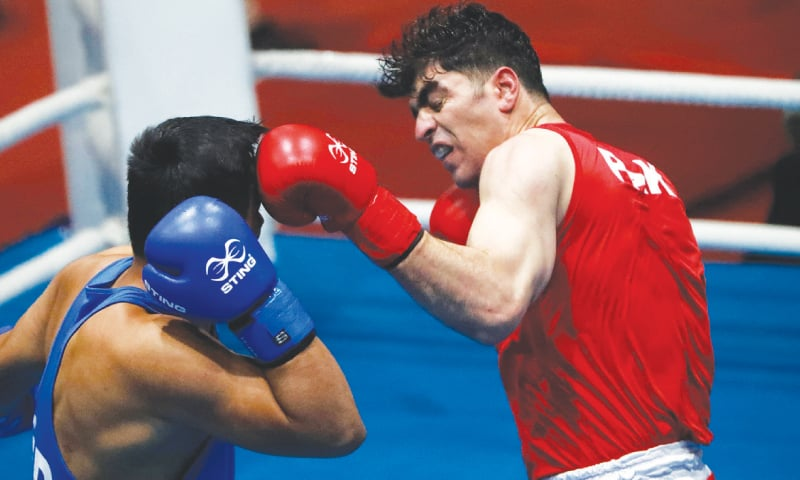 PAKISTAN'S Sanaullah lands a left on Gaurav Chauhan of India during their 91kg welterweight boxing final at the South Asian Games on Monday. Chauhan won the bout.—AP
