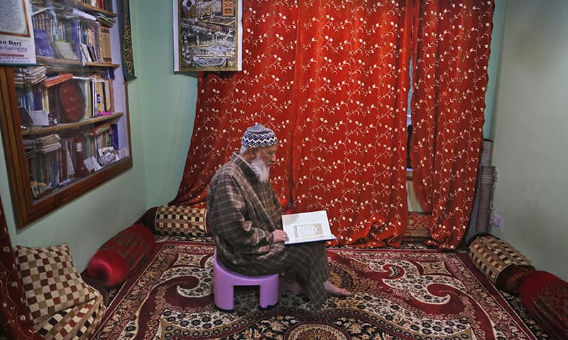 In this November 19, 2019 photo, Mohammed Yasin Bangi, muezzin at grand Jamia Masjid, city's main mosque reads holy Quran inside his home in Srinagar, Indian-occupied Kashmir. — AP