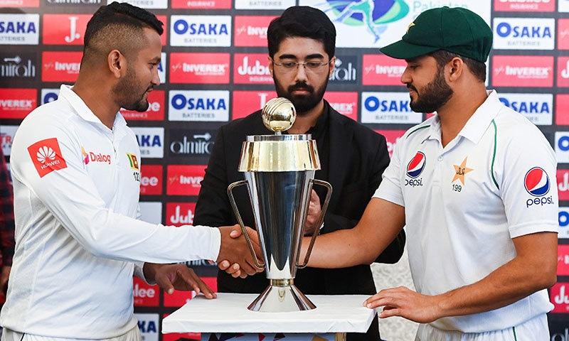 پاکستان کے کپتان اظہر علی اور سری لنکن قائد دمتھ کرونارتنے سیریز کی ٹرافی کی تقریب رونمائی کے موقع پر مصافحہ کر رہے ہیں— فوٹو: اے ایف پی