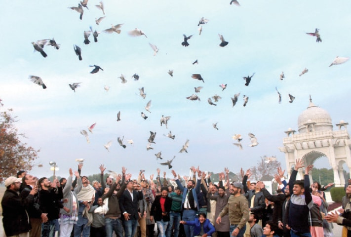 Civil society activists release pigeons in F-9 Park in Islamabad on Tuesday to mark the 71st anniversary of the UN Declaration of Human Rights and also inform the international community about the deplorable situation in India-held Kashmir. — Photo by Mohammad Asim