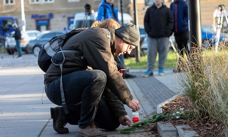 A man lights a candles in front of the Faculty Hospital in Ostrava, eastern Czech Republic on December 10, after a gunman opened fire on the morning, killing six people.  — AFP