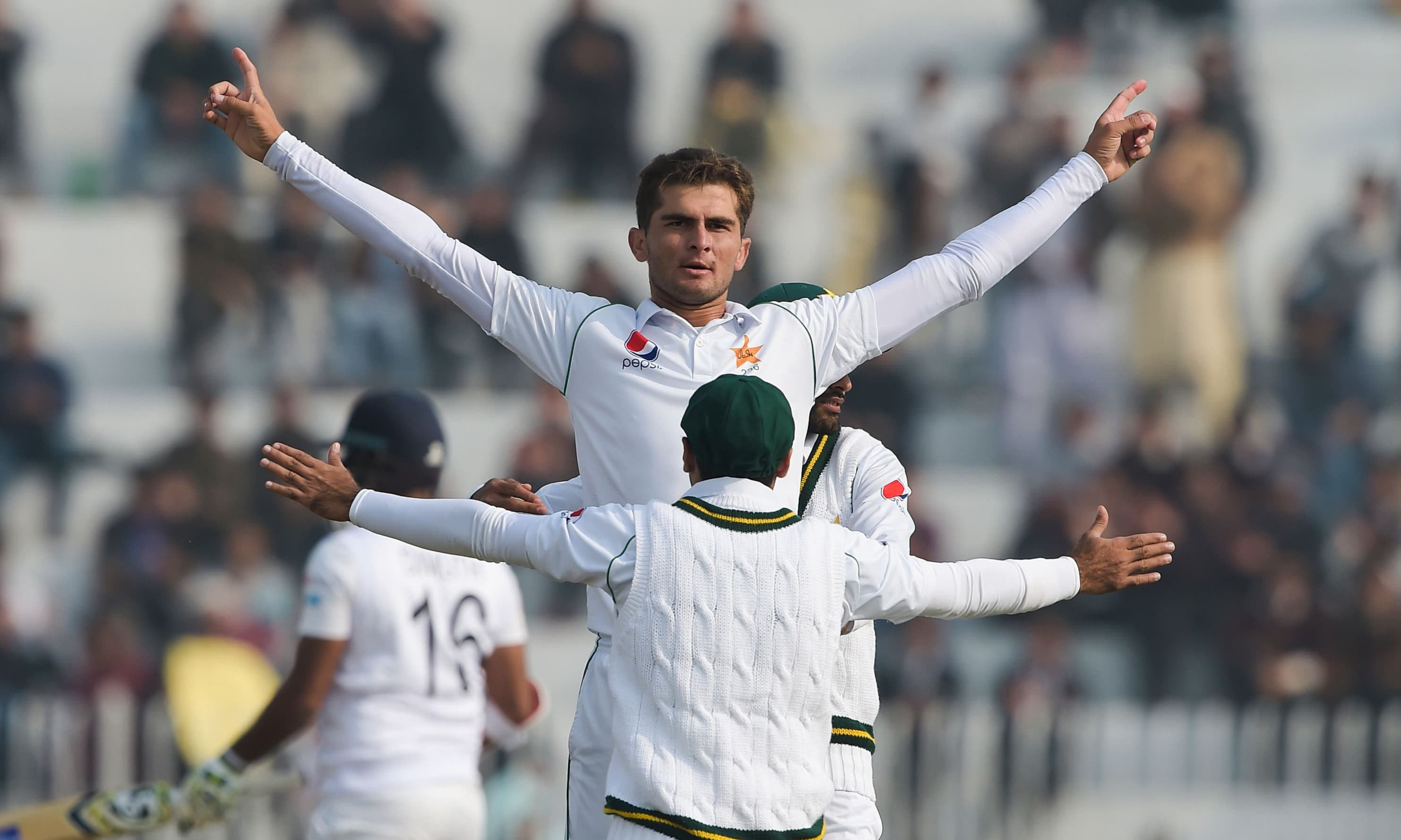 Pakistan's Shaheen Shah celebrates with teammates after dismissing Sri Lanka's Dimuth Karunaratne during the first day of the first Test cricket match between Pakistan and Sri Lanka at the Pindi Cricket Stadium in Rawalpindi on Dec 11. — AFP