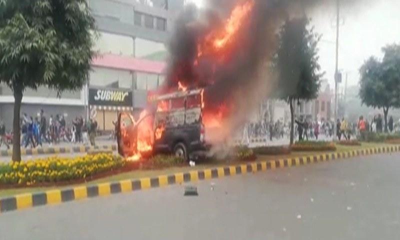 مشتعل افراد نے پولیس موبائل کو بھی آگ لگادی—تصویر: ڈان نیوز