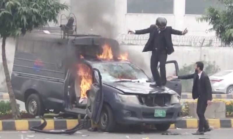 A protester stands on a police mobile that was set on fire. — DawnNewsTV