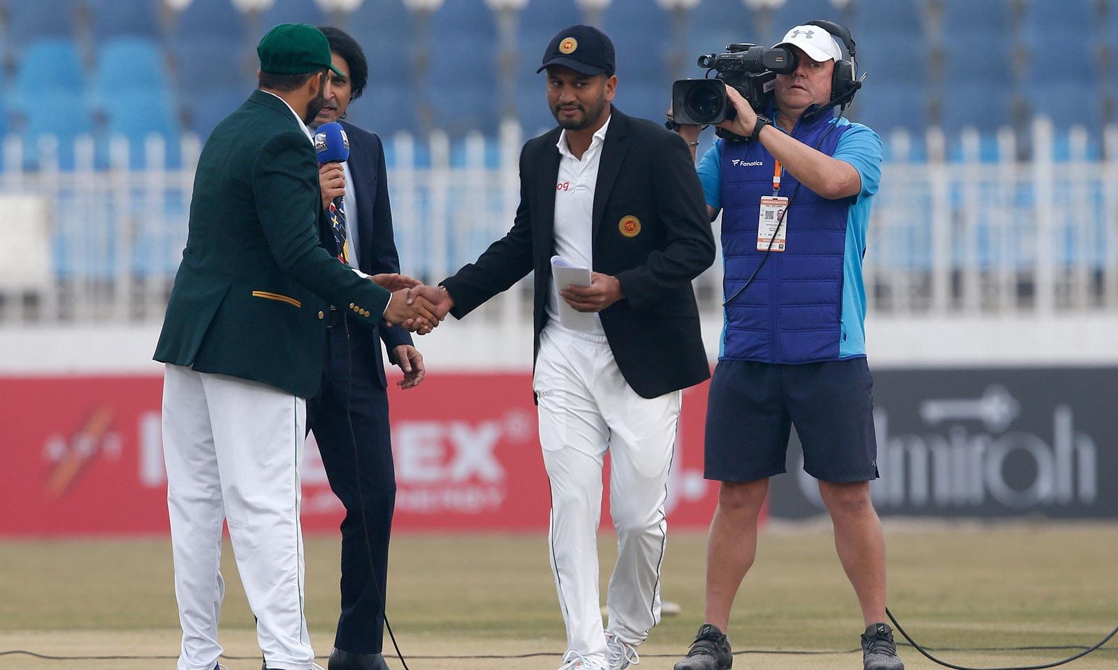 میچ میں ٹاس جیتنے کے بعد سری لنکن کپتان اپنے پاکستانی ہم منصب اظہر علی سے مصافحہ کر رہے ہیں— فوٹو: اے پی