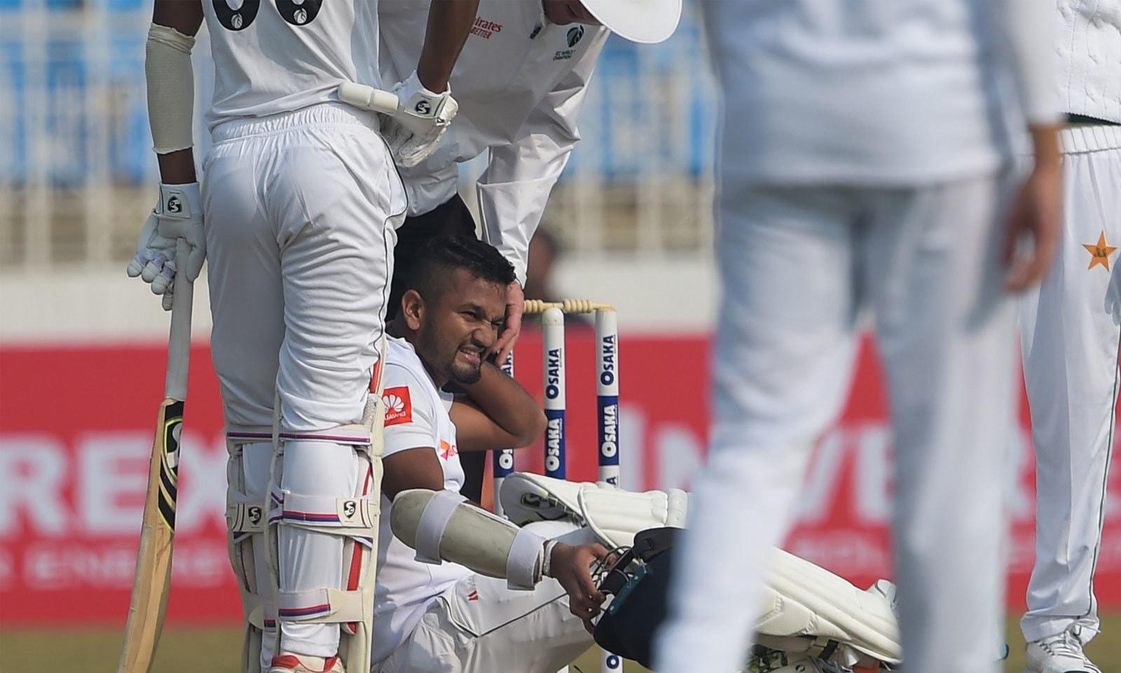 پاکستان فاسٹ باؤللر نسیم شاہ کی گیند سری لنکن کپتان دمتھ کرونارتنے کی گردن پر لگی— فوٹو: اے ایف پی