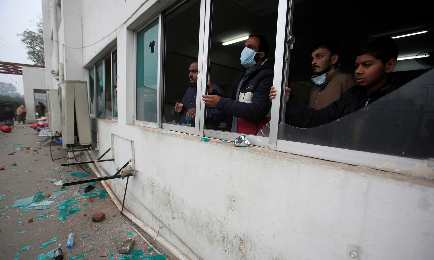 Men stand as they look outside from broken windows after a group of lawyers stormed the Punjab Institute of Cardiology. — Reuters