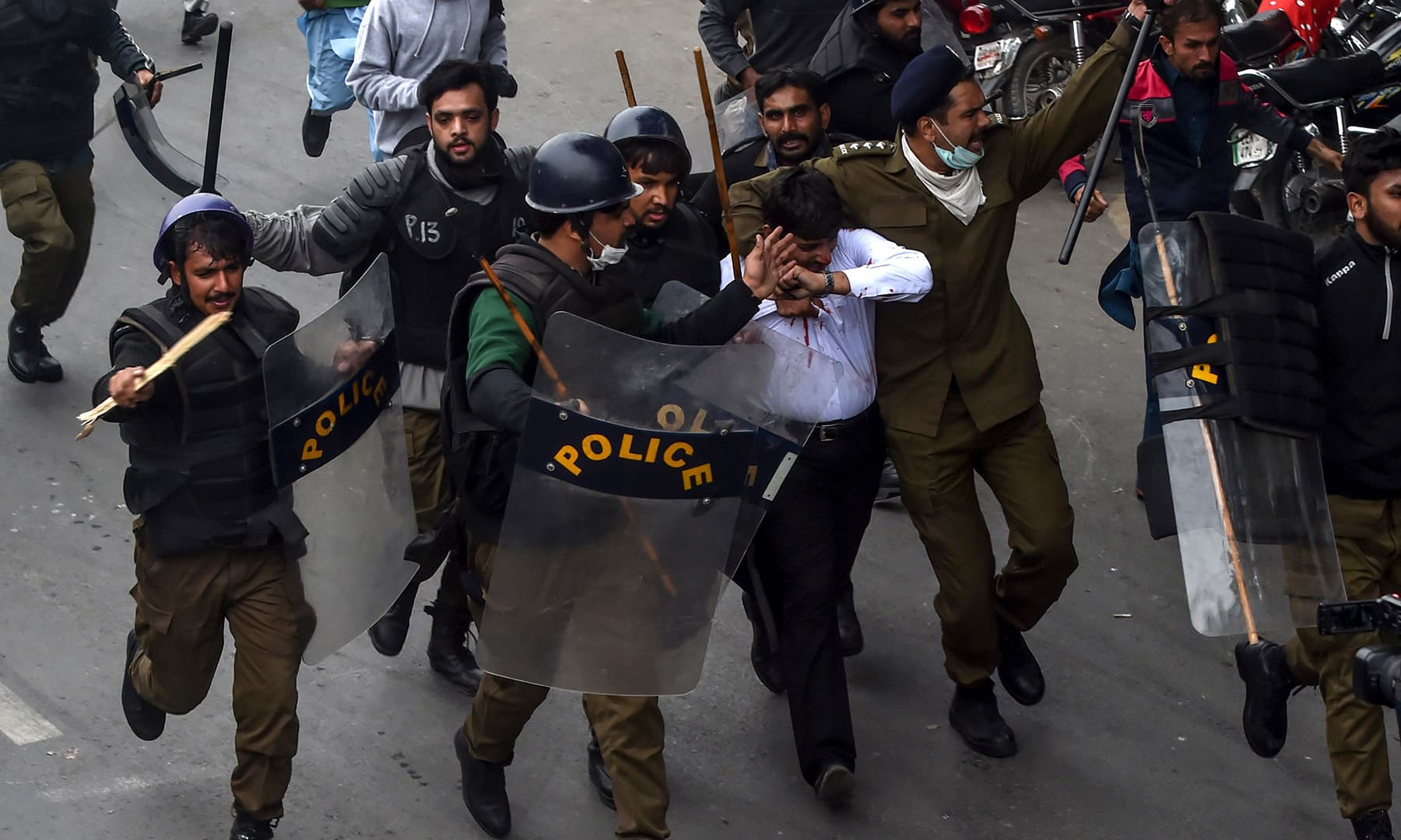 Policemen detain a lawyer (C in white shirt) following a clash between lawyers and doctors in Lahore. — AFP